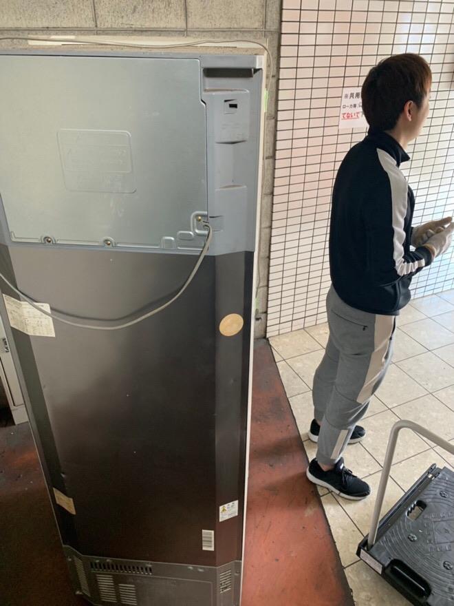 大きな冷蔵庫を運ぶ姿